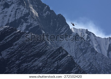 Rescue hellicopter over Machhapuchchhre mountain - Fish Tail in English is a mountain in the Annapurna Himalya, Nepal - stock photo
