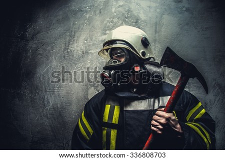 Rescue man in firefighter uniform with oxygen mask on his face and red axe in his arm.
