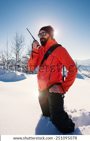 Rescue man talking with portable radio on mountain snow landscape. Back light image. - stock photo