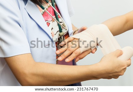 Rescuer bandaging upper limb of young woman - stock photo