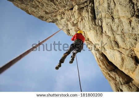 Rescuer climbs on rock - stock photo