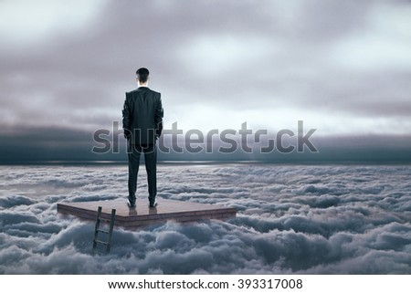 Research concept with man on brick pedestal in dull cloudy sky - stock photo
