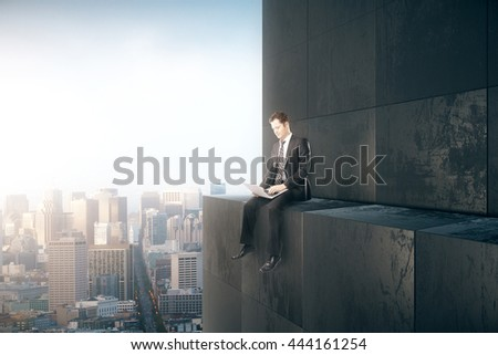 Research concept with thoughtful businessman sitting on skyscraper and and using laptop computer on city background