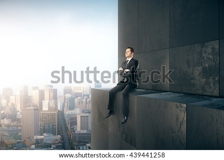 Research concept with thoughtful businessman sitting on skyscraper and looking into the distance on city background