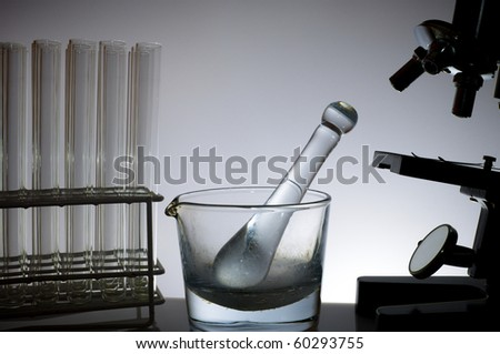 research microscope, test tubes and a glass mortar - stock photo