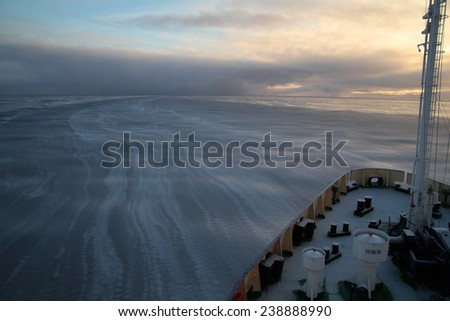 Research vessel in Arctic sea with forming young ice - stock photo