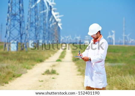 researcher analyzes readouts on wind power station - stock photo