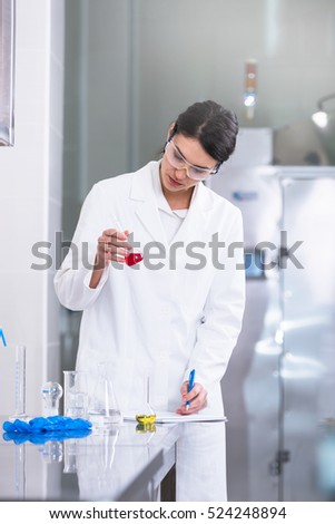 Researcher doing chemical test in the laboratory and making notes