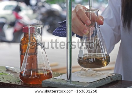 researcher is doing the experiment, the titration of the reagent in the flask - stock photo