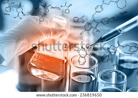 Researcher is dropping the reagent into test tube, with chemical equations background, in laboratory - stock photo