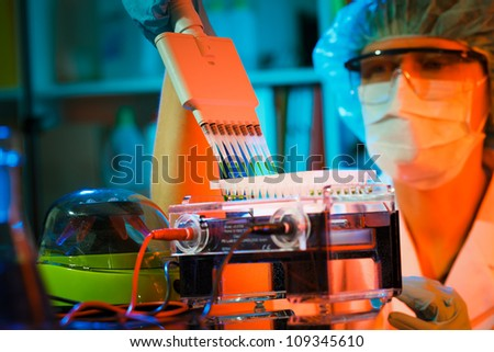 Researcher using a multi-pipette to fill a multiwell sample tray in a biochemistry lab. - stock photo