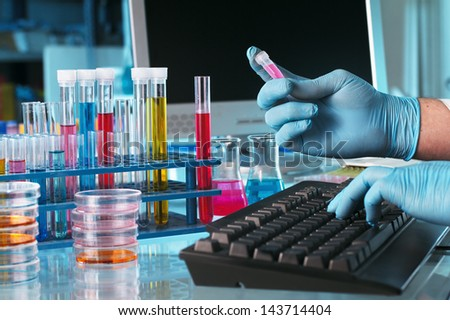 researcher with a pipe in hand typing data to the computer lab - stock photo