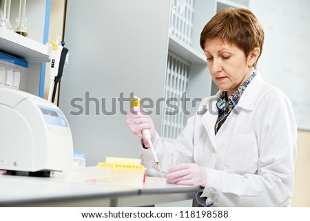 Researcher with dropper of medicine during pharmaceutical laboratory blood test examination - stock photo