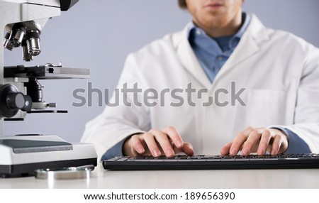 Researcher working at desk and typing on a keyboard, with microscope and magnifier. - stock photo