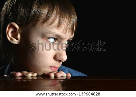 resentful young boy on a black background - stock photo