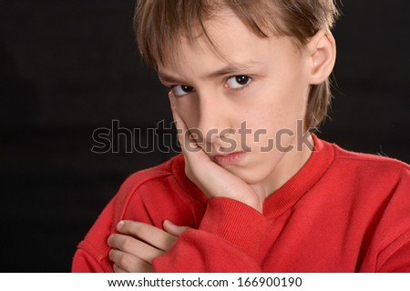 resentful young guy in the red shirt on a black background - stock photo