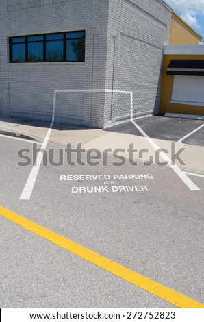 RESERVED PARKING FOR DRUNK DRIVER spot which is painted into the corner of a building showing the dangers of driving while drunk