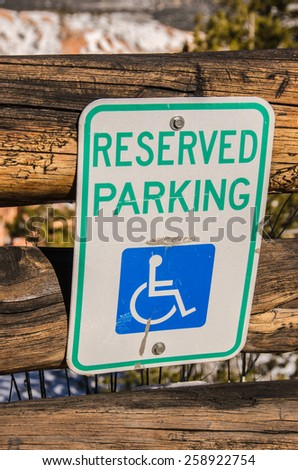 Reserved parking sign for handicapped people denoted by the wheelchair on the sign - stock photo