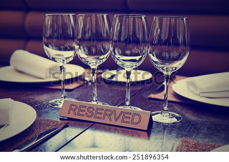 Reserved plate on an arranged restaurant table, toned image - stock photo