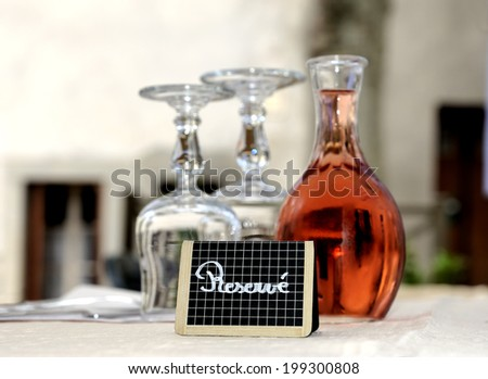Reserved sign at a restaurant table in France.With glasses and a decanter filled with rose wine - stock photo