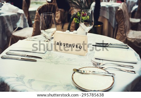 Reserved sign on the table in a fancy restaurant - stock photo