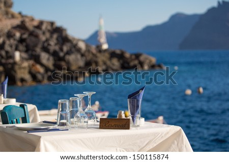 Reserved table in front of the aegean sea, in the blurred background , you see the shore-line of Santorini. - stock photo