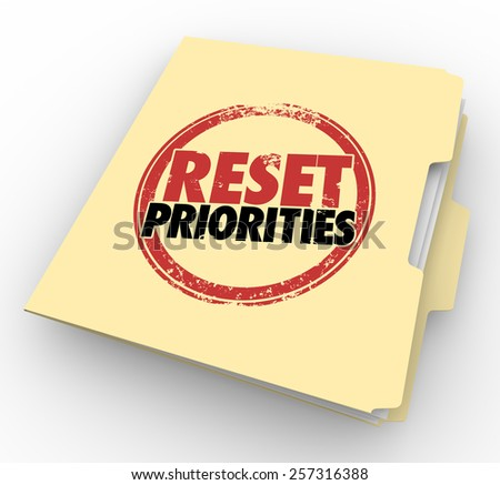 Reset Priorities words stamped on a manila folder to illustrate a change in the most important jobs or tasks to handle first in order - stock photo