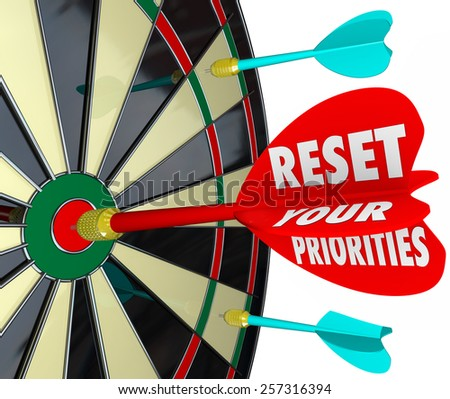 Reset Your Priorities words on a dart board to illustrate targeting most important jobs or tasks and changing the order to get them done - stock photo
