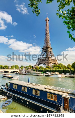 Residential barge and tourist ships on the Seine near the Eiffel Tower, Paris. - stock photo