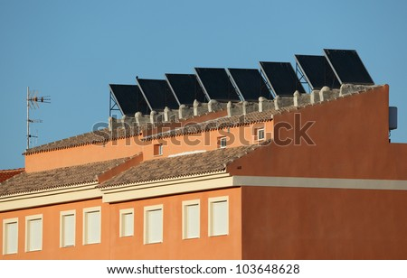 Residential building with solar panels on the roof - stock photo