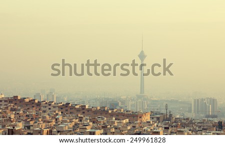 Residential buildings in front of Milad Tower in air-polluted skyline of Tehran. - stock photo