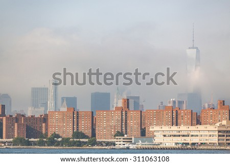 Residential buildings in New York with modern skyscrapers on background, partially covered by fog. Photo taken in the early morning from East River coast - stock photo