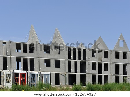 Residential buildings under construction against a clear blue sky