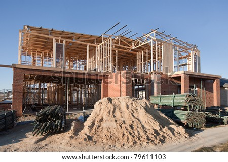 Residential construction site with partially completed home - stock photo