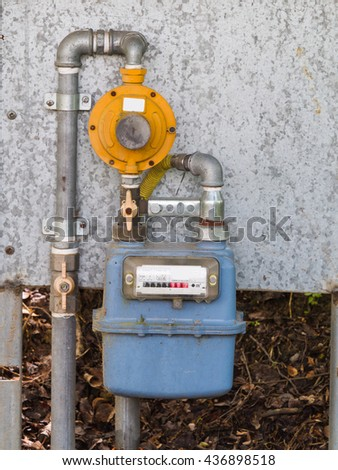 residential diaphragm external gas meter with regulator, shut-off  valves and pipes - stock photo