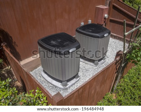 Residential heating and air conditioner compressor units near residential house - stock photo