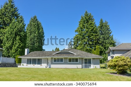 Residential house on sunny day with landscaped lawn in front and blue sky background. Suburban house with concrete driveway and asphalt road in front.