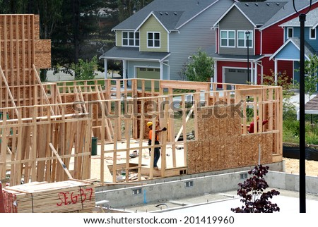 residential house under construction by male worker - stock photo