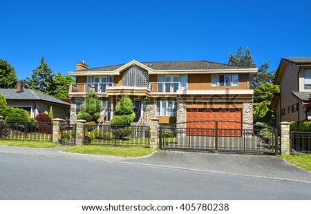 Residential house with wide garage, landscaped front yard, and metal fence in front.  Beautiful house with topiary trees on green lawn in front and blue sky background. House in suburb of Vancouver. - stock photo
