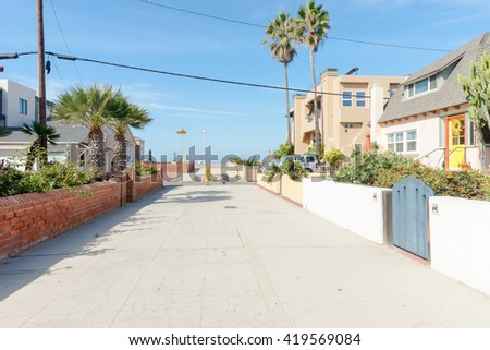 Residential lane lined by fences, homes and gates in seaside town Hermosa Beach, California USA