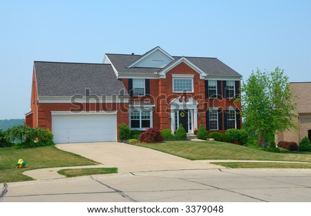 Residential 2-story brick home in an upscale suburban neighborhood. - stock photo