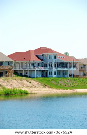 Residential Upscale Lakeside House - A residential suburban home in an upscale neighborhood on a lake in the summertime.