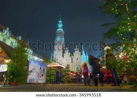 Residents and tourists visit the Christmas market in the Old Market Square in Wroclaw, Poland, EU. A long time shutter exposure. - stock photo
