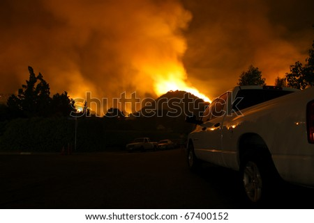 Residents of a neighborhood sit by and watch a fire threaten their homes. - stock photo