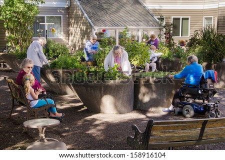 Residents of an assisted-living facility tend their gardens in wheelchair accessible containers. - stock photo