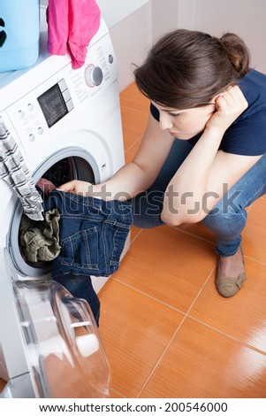 Resigned housekeeper has to do the laundry - stock photo