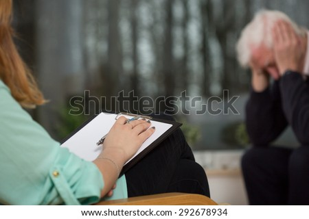 Resigned man during visit at psychologist's office - stock photo