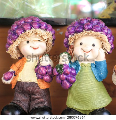 Resin Dolls with Grape Hat, Selective Focus, Blur Background