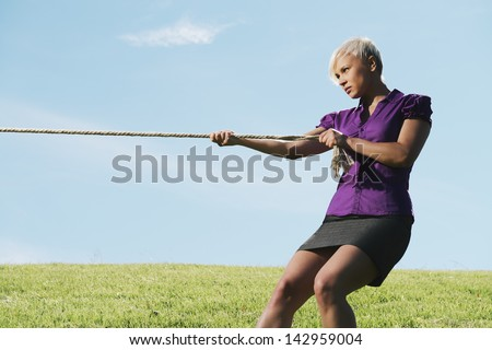 resolute business woman pulling rope against blue sky, symbol of power and determination. Copy space, side view - stock photo