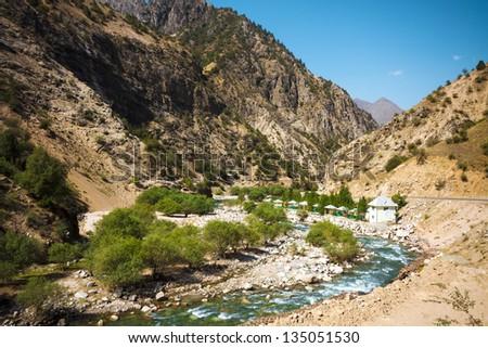 Resort along Mountain moraine river under cloudy sky in summertime in Takob, Tajikistan - stock photo
